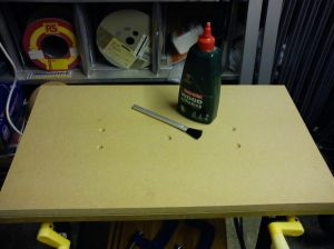Lower layer of MDF tabletop showing countersunk screw heads