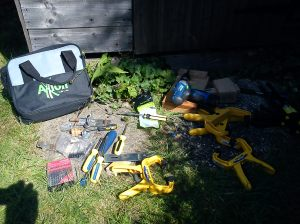 Selection of tools outside shed during hasp fitting and bolt relocation