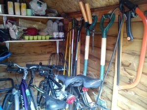 Garden tools locked to bikes in shed