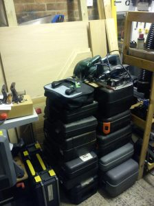 Power tools stacked in front of MDF leaning on shelves