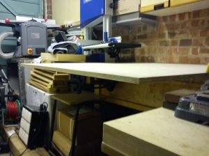 Plywood on bench supported at front by open vice